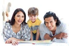Livro de leitura feliz da família junto Fotos de Stock Royalty Free