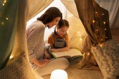 Livro de leitura feliz da família na barraca das crianças em casa fotos de stock