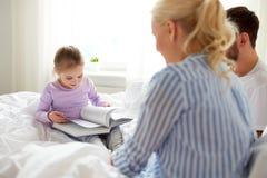Livro de leitura feliz da família na cama em casa Imagem de Stock Royalty Free