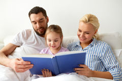 Livro de leitura feliz da família na cama em casa Fotografia de Stock