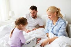 Livro de leitura feliz da família na cama em casa Fotos de Stock Royalty Free