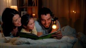 Livro de leitura feliz da família na cama na noite em casa vídeos de arquivo
