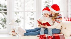 Livro de leitura feliz da filha da mãe e da criança da família em wi do inverno fotos de stock
