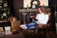 Livro de leitura feliz da jovem mulher na frente da árvore de Natal Fotos de Stock