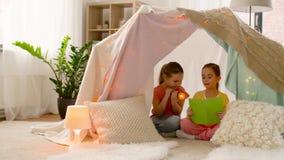 Livro de leitura feliz das meninas na barraca das crianças em casa vídeos de arquivo