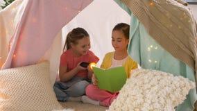 Livro de leitura feliz das meninas na barraca das crianças em casa video estoque
