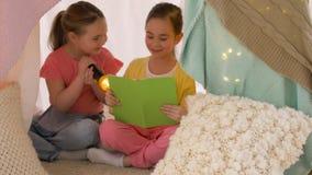 Livro de leitura feliz das meninas na barraca das crianças em casa filme