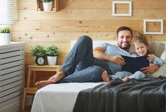 Livro de leitura feliz do pai e da filha da família na cama Fotografia de Stock