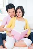 Livro de leitura grávido dos pares do asiático imagens de stock