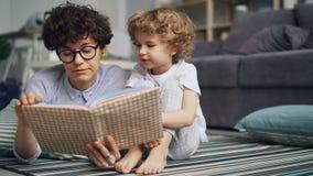 Livro de leitura de inquietação da mamã ao menino curioso pequeno que relaxa no assoalho na casa clara