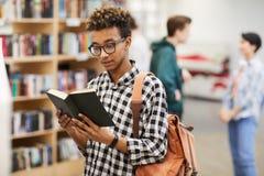 Livro de leitura inteligente do indivíduo na biblioteca fotografia de stock
