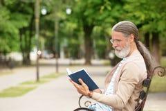 Livro de leitura maduro considerável do homem no banco imagem de stock royalty free