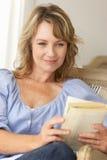Livro de leitura meados de da mulher da idade imagens de stock