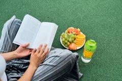 Livro de leitura no gramado, vista superior da mulher sobre o ombro fotos de stock royalty free