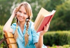 Livro de leitura novo bonito da menina do estudante Fotografia de Stock