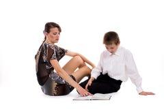 Livro de leitura novo da matriz no assoalho com seu filho isolado no whit Foto de Stock Royalty Free