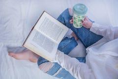 Livro de leitura novo da menina do estudante no livro acolhedor da cama e guardar nos pés com pés desencapados e café quente bebe imagens de stock
