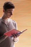 Livro de leitura novo do estudante masculino Fotos de Stock