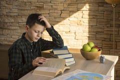 Livro de leitura novo do menino e estudo na tabela em casa imagens de stock