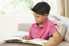 Livro de leitura novo do menino em casa Foto de Stock