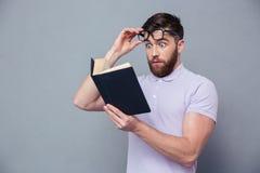 Livro de leitura ocasional surpreendido do homem Imagem de Stock