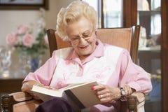 Livro de leitura sênior da mulher Imagens de Stock