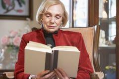 Livro de leitura sênior da mulher Imagem de Stock