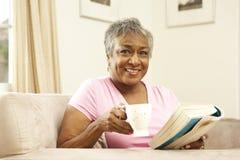 Livro de leitura sênior da mulher com bebida Fotos de Stock