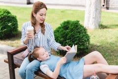 livro de leitura de sorriso da criança com mãe próximo por ao descansar no banco junto fotografia de stock