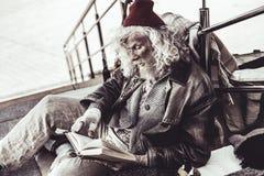 Livro de leitura sujo velho do preguiçoso que transeunte que dá o foto de stock