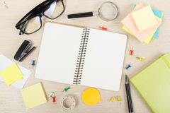 Livro de nota aberto da placa branca Mesa da tabela do escritório com grupo de fontes coloridas, copo, pena, lápis, flor, notas,  Foto de Stock Royalty Free