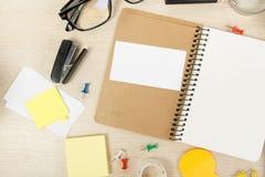 Livro de nota aberto da placa branca Mesa da tabela do escritório com grupo de fontes coloridas, copo, pena, lápis, flor, notas,  Fotografia de Stock Royalty Free