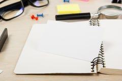 Livro de nota aberto da placa branca Mesa da tabela do escritório com grupo de fontes coloridas, copo, pena, lápis, flor, notas,  Imagem de Stock