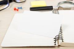 Livro de nota aberto da placa branca Mesa da tabela do escritório com grupo de fontes coloridas, copo, pena, lápis, flor, notas,  Imagem de Stock Royalty Free