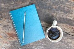 Livro de nota azul com copo de café Fotografia de Stock
