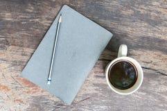 Livro de nota cinzento com copo de café Imagem de Stock Royalty Free