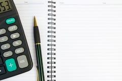 Livro de nota com calculadora e pena Fotografia de Stock Royalty Free
