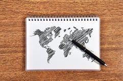 Livro de nota com mapa de mundo Fotos de Stock