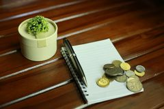 livro de nota, pena, moedas e decoração isolados no fundo de madeira Foto de Stock