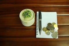 livro de nota, pena, moedas e decoração isolados no fundo de madeira foto de stock royalty free