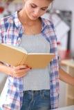 Livro de receitas da leitura da jovem mulher na cozinha, Fotografia de Stock Royalty Free