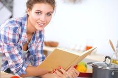 Livro de receitas da leitura da jovem mulher na cozinha, Imagens de Stock