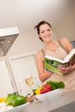 Livro de receitas da leitura da mulher nova na cozinha Foto de Stock