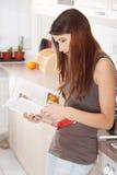 Livro de receitas da leitura da mulher nova na cozinha Fotografia de Stock