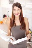Livro de receitas da leitura da mulher nova na cozinha Imagem de Stock Royalty Free