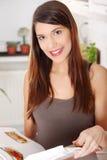Livro de receitas da leitura da mulher nova na cozinha Imagens de Stock Royalty Free