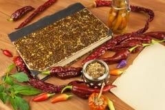Livro de receitas e especiarias na tabela de madeira Livro de receitas e ingredientes Alho, pimentas de pimentão e cebola Ingredi Fotos de Stock Royalty Free