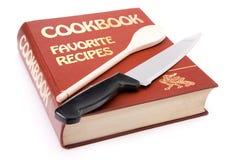 Livro de receitas grande com colher e a faca de cozinha de madeira fotografia de stock royalty free