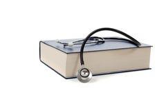 Livro de referência médico com um estetoscópio no branco foto de stock