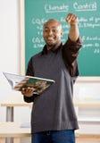 Livro de texto da terra arrendada do professor que aponta ao estudante Foto de Stock Royalty Free